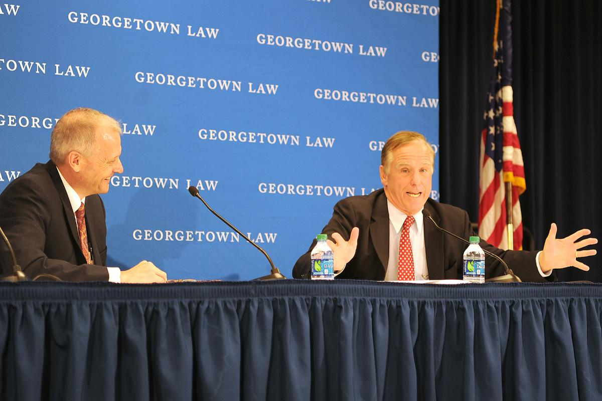 Two men speaking at a panel.