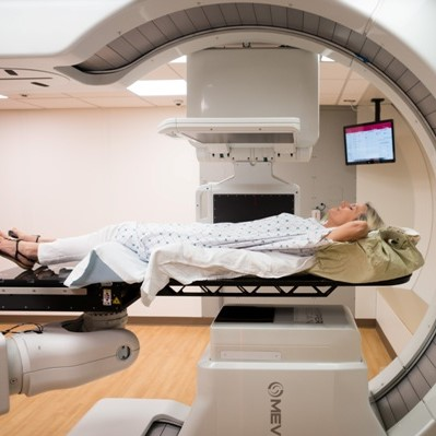 A women laying down on a proton therapy machine.