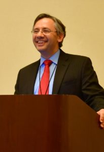 Man smiling at a podium during the Ruesch symposium.